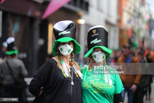 Two women in clover patterned face masks near the Temple bar in Dublin on St Patrick's day
