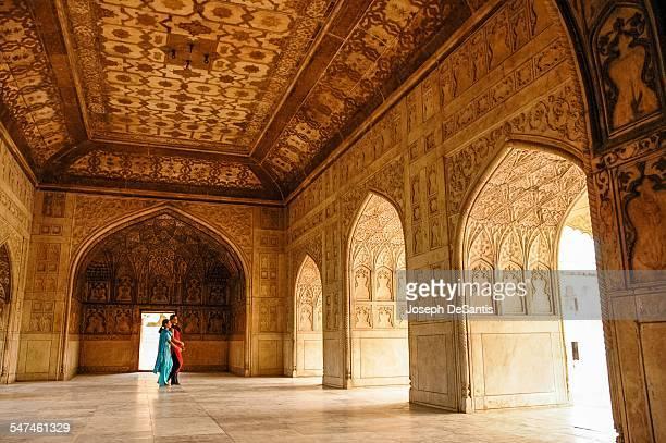 Two women in colorful Sari dresses walking in the ornate Agra Fort Agra Uttar Pradesh India