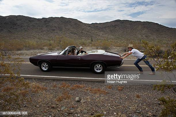 Two women in convertible car being pushed by man