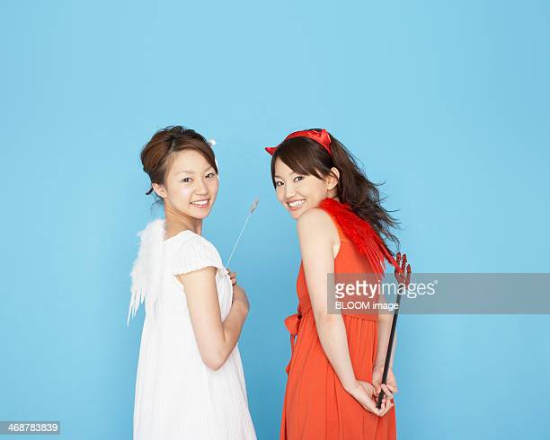 two women in devil and angel costume - devil costume stock photos and pictures