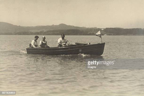 Two women in dirndl dresses and a man in a motor boat on a lake in Bavaria or Upper Austria About 1930 Photograph