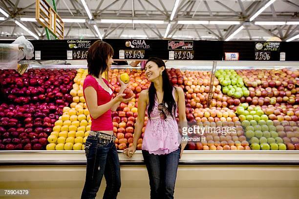 Two women in fruit market, smiling