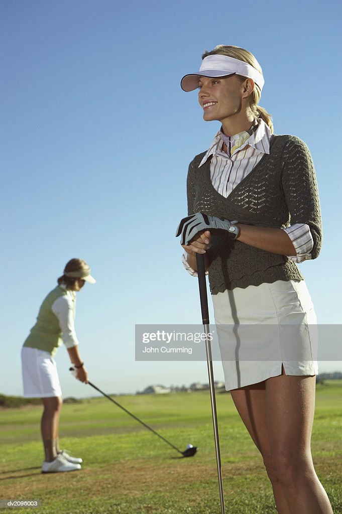 Two Women in Golf wear Standing on a Putting Green : Stock Photo