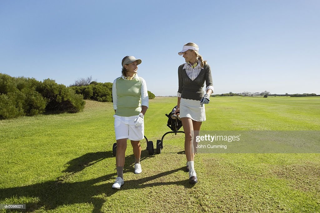 Two Women in Golf wear Walking and Pulling a Golf bag : Stock Photo