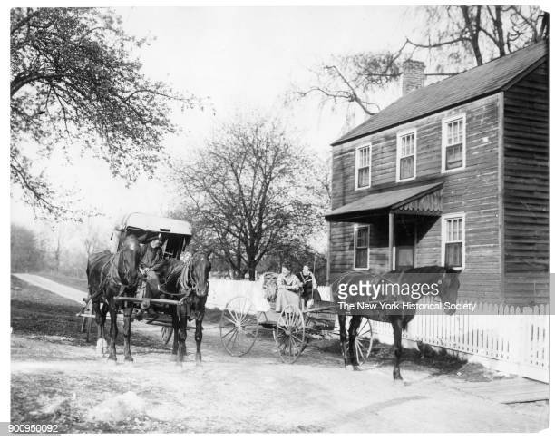 Two women in horsedrawn carriage chat with fruit peddler in covered horsedrawn wagon outside of 2story wooden house with white picket fence Arkansas...