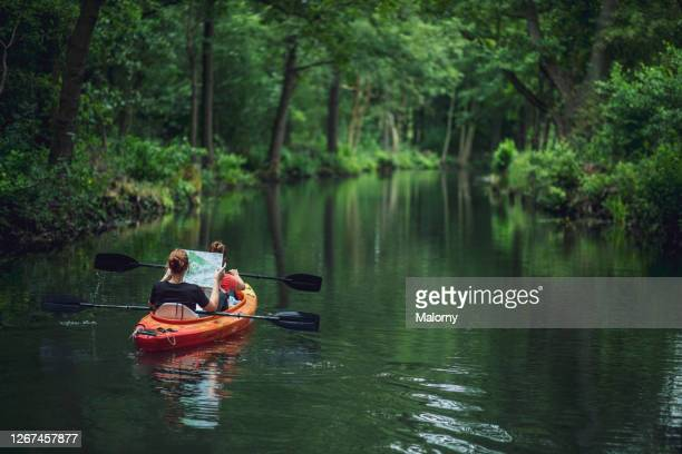 two women in kayak reading a map and floating through the forest. germany, brandenburg, spreewald, luebbenau - spreewald stock pictures, royalty-free photos & images