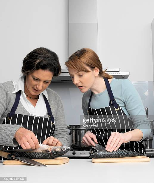 Two women in kitchen gutting fish on chopping boards