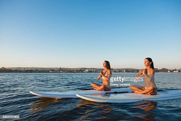 Two women in lotus position on paddleboards, Mission Bay, San Diego, California, USA