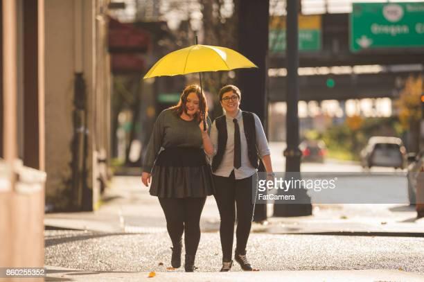 deux femmes dans l'amour marchant sur le trottoir sous la pluie - gay love photos et images de collection
