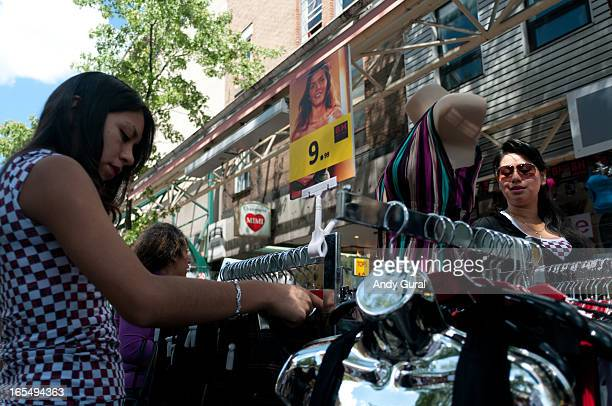 CONTENT] Two women in mixed light are at sidewalk sale and browsing a rack with trousers