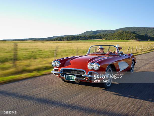 two women in red convertible - convertible stock photos and pictures