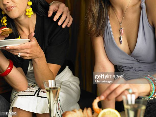 two women in restaurant eating appetizers, mid section - clubkleding stockfoto's en -beelden