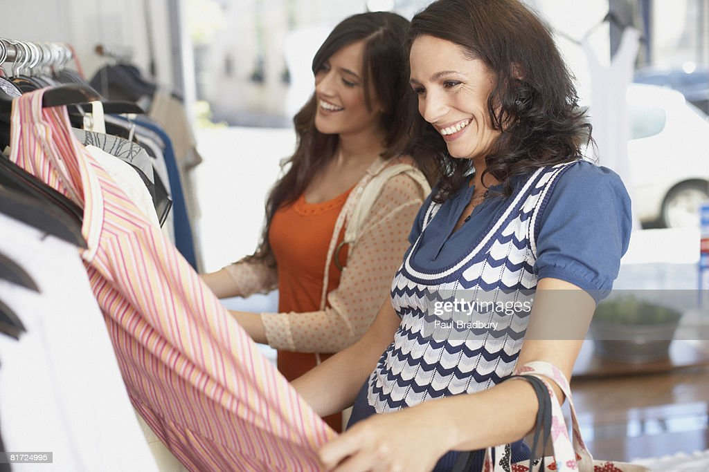 Two women in store looking at dresses smiling : Stock Photo