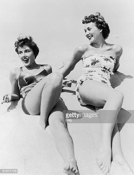 Two women in swimming costumes relax on the beach circa 1935