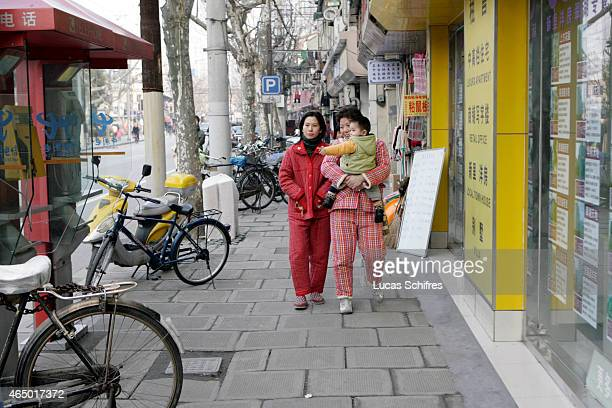 Two women in their pyjamas walk a baby on January 8 2009 in Shanghai China