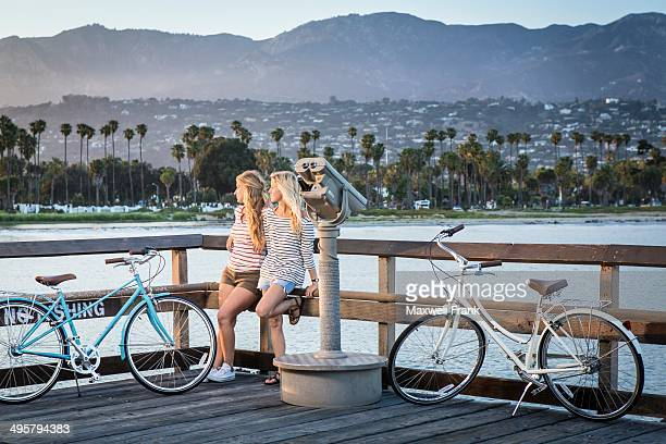 Two women in their twenties taking a break from riding their bikes. They are resting on the railing watching the sun go down with mountains and ocean in the background.