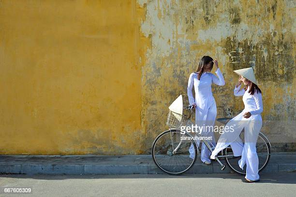 Two women in traditional clothing standing in street talking, Hoi An, Vietnam