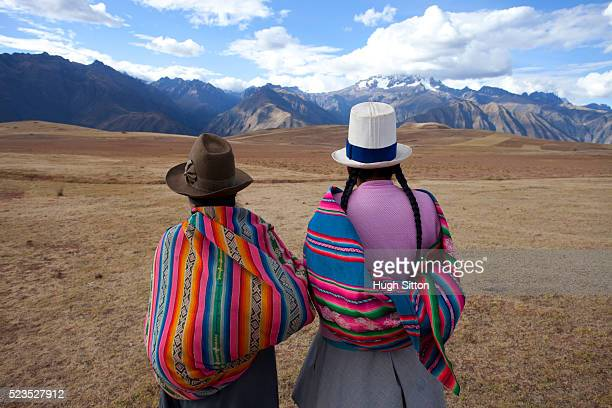 Two women in traditional costume walking in the mountains, near Moray. Peru.