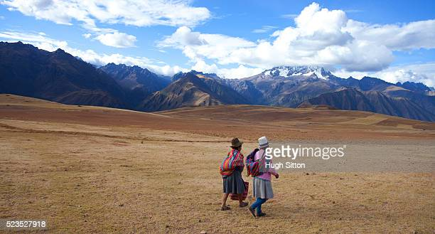 two women in traditional costume walking in the mountains, near moray. peru. - hugh sitton stock pictures, royalty-free photos & images