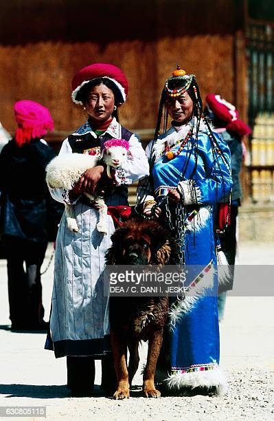 Two women in traditional dress with a dog and lamb, Shangri-La City in Yunnan, China.
