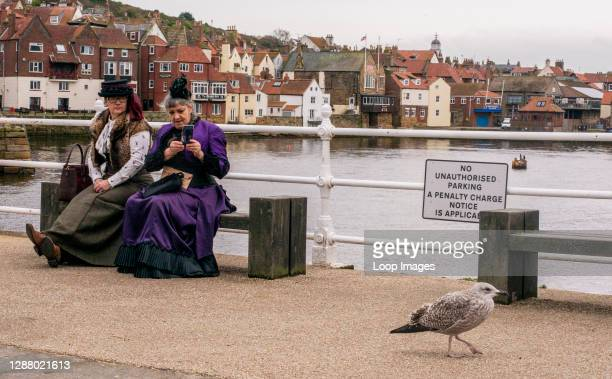 Two women in traditional Goth costumes taking photograph of seagull at Whitby Goth Weekend Festival in Whitby in North Yorkshire.