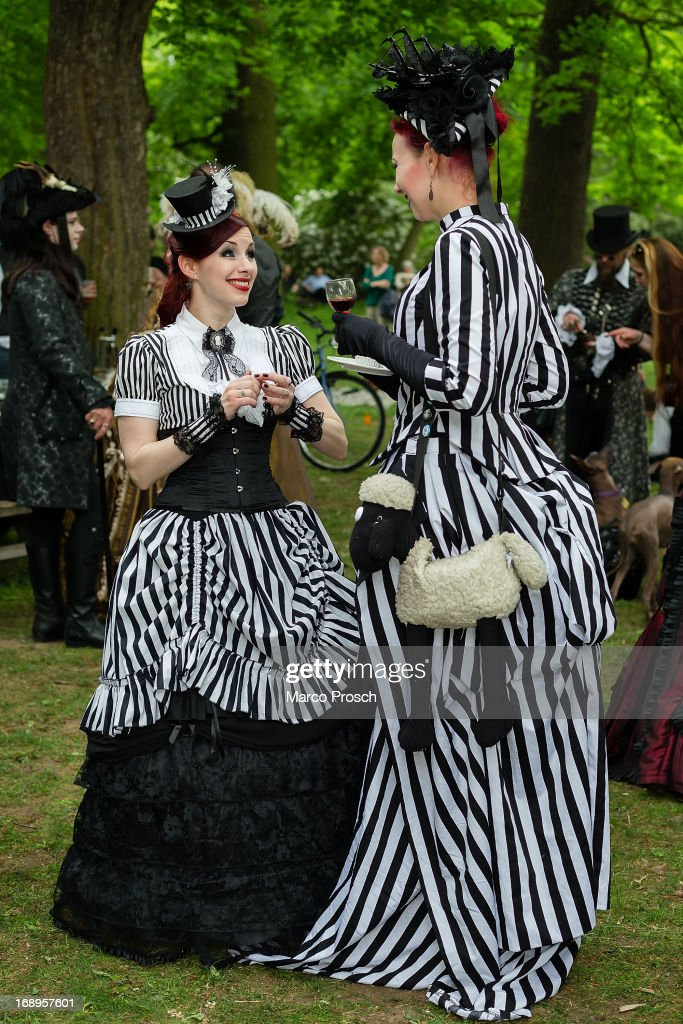 Two women in Victorian clothing and with a shawn-the-sheep-bag chat during the traditional park picnic on the first day of the annual Wave-Gotik Treffen, or Wave and Goth Festival, on May 17, 2013 in Leipzig, Germany. The four-day festival, in which elaborate fashion is a must, brings together over 20,000 Wave, Goth and steam punk enthusiasts from all over the world for concerts, readings, films, a Middle Ages market and workshops.