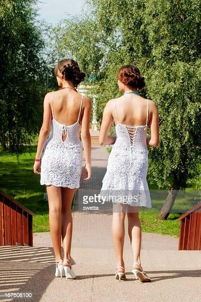 Two women in white dress,rear view
