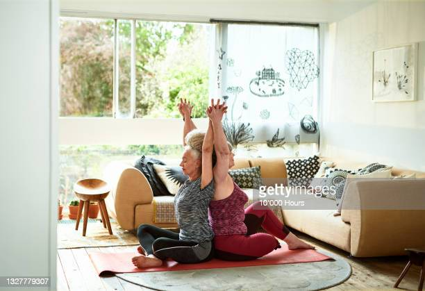two women in yoga pose at home - human arm stock pictures, royalty-free photos & images
