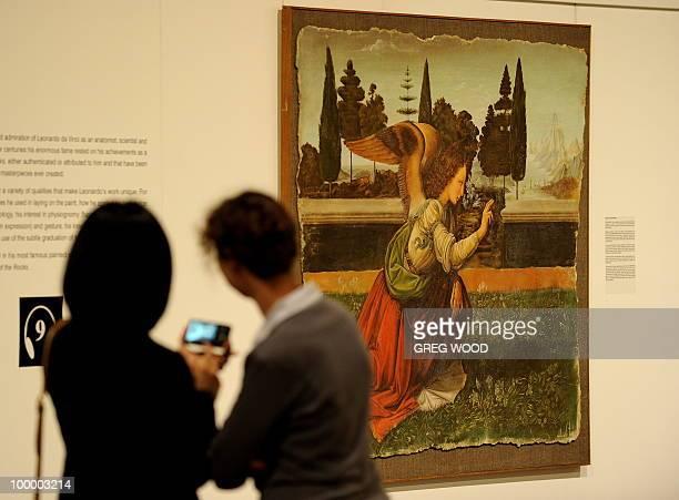 Two women inspect a reproduction of the Leonardo da Vinci Annunciation painting by Florentine artist Antonio de Vito which forms part of the Leonardo...
