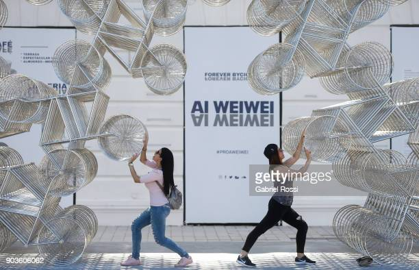 Two women interact with the installation Forever Bicycles during the Inoculation Exhibition of Chinese contemporary artist Ai Weiwei at Fundacion...