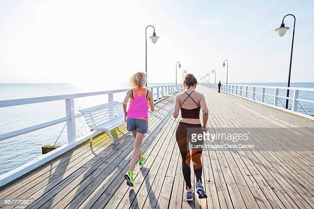 two women jogging along a jetty - 背景に人 ストックフォトと画像