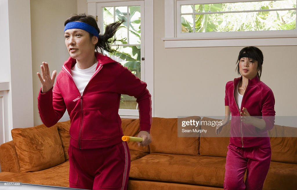 Two women jogging in place in the living room : Stock Photo