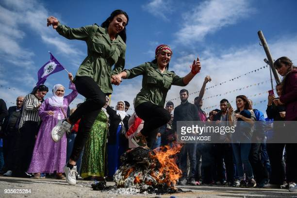 TOPSHOT Two women jump over a bonfire during a Kurdish celebration of Nowruz the Persian calendar New Year in Istanbul on March 21 2018