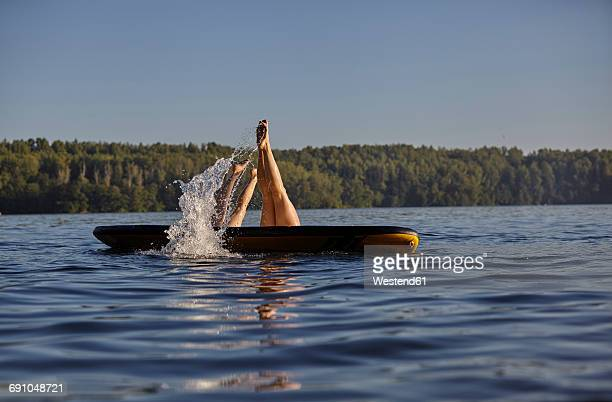 two women jumping into water from paddleboard - sport aquatique photos et images de collection
