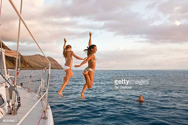 Two women jumping off sail boat
