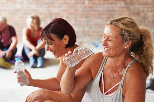 Two women laughing and drinking from water bottles in the gym - gettyimageskorea