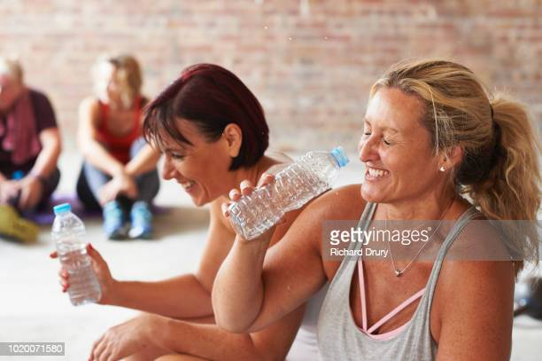 Two women laughing and drinking from water bottles in the gym