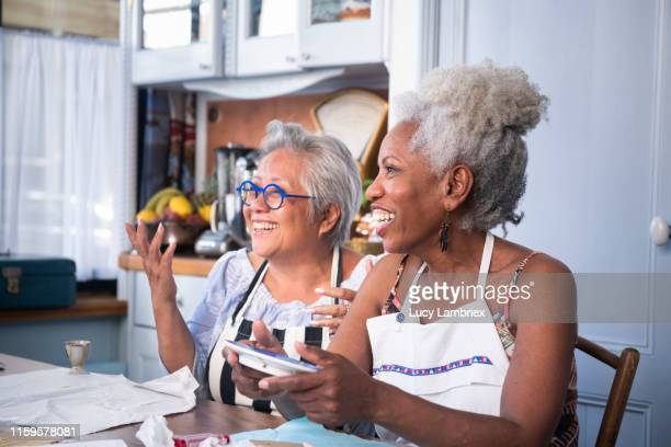 Two women laughing and joking at a new kintsugi workshop: fixing broken ceramics with golden glue
