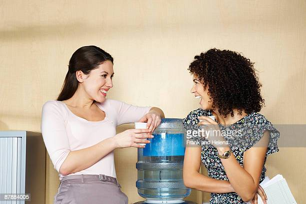 Two women laughing by water cooler