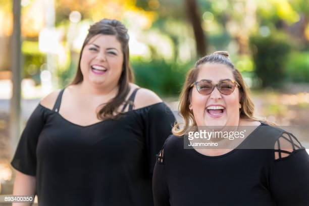 two women laughing - arab women fat stock pictures, royalty-free photos & images