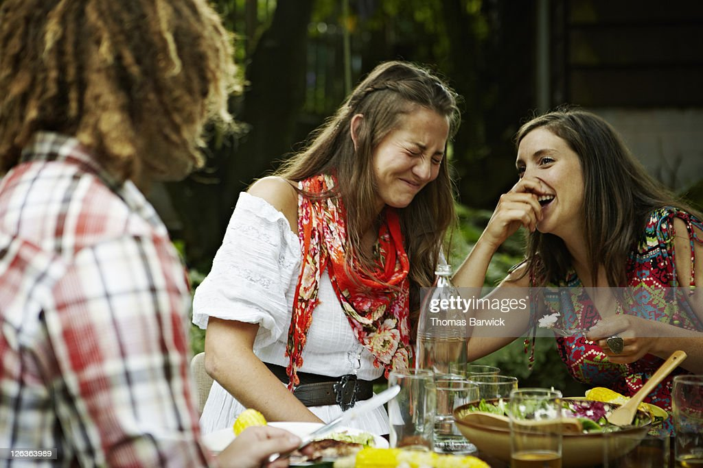 Two women laughing together at dining table : Stock Photo