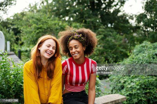 two women laughing together - female friendship stock pictures, royalty-free photos & images