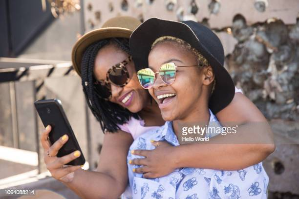 two women laughing while looking at smart phone - hoofddeksel stockfoto's en -beelden