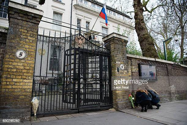 Two women lay flowers to mourn the murder of Russia's Ambassador to Turkey Andrei Karlov outside the Russian embassy on December 20 2016 in London...