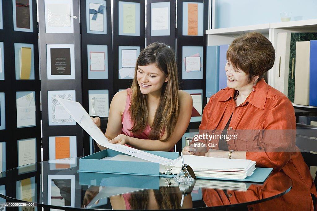 Two women leafing through folder in shop : Stockfoto