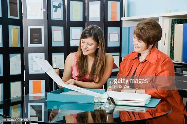 Two women leafing through folder in shop