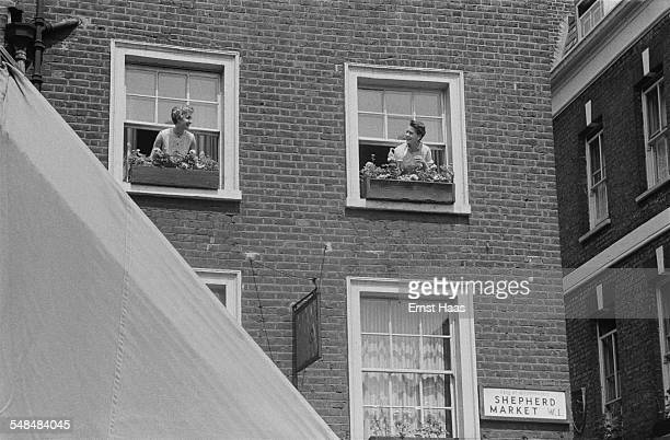 Two women leaning out of their windows for a chat on Shepherd Market Mayfair London circa 1953