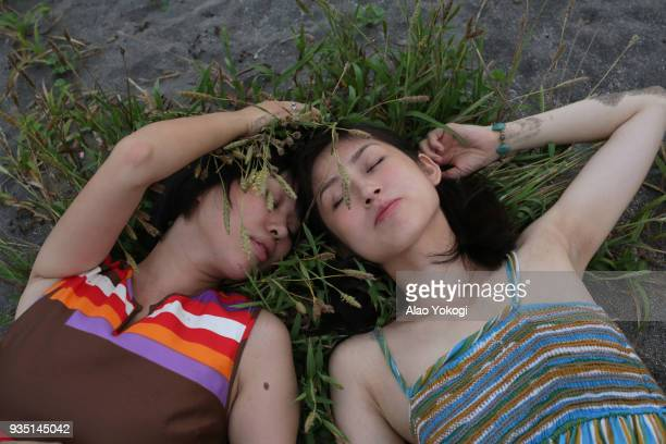 Two women lie on the beach