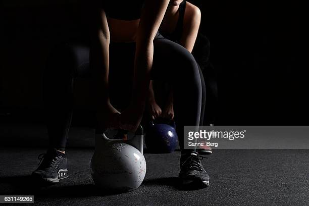 Two women lifting kettle bells in gym