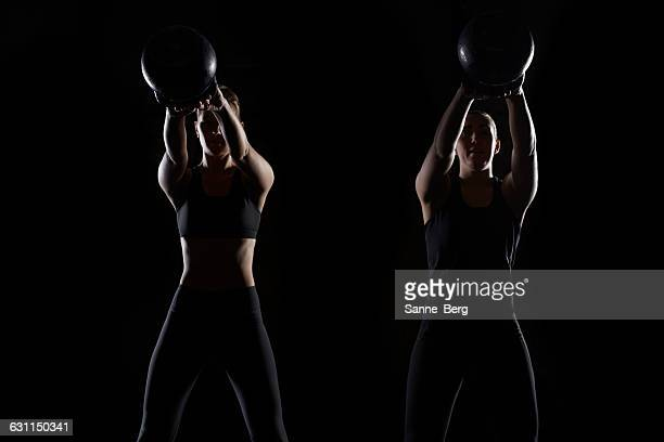 Two women lifting kettlebells in gym